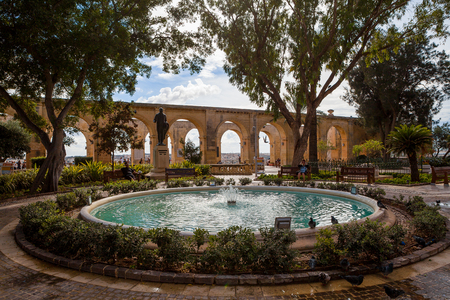 Sparkling fountain under peaceful trees and limestone arches on the background, Upper Barrakka Gardens park, Capital city of Malta, Valletta. Stock fotó