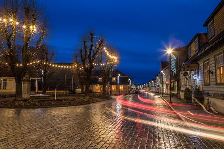 HAAPSALU, ESTONIA - 25 de octubre, 2016: Plaza de la ciudad pequeña con pavimento y trazadores en la noche. Patrimonio de la Europa norteña.