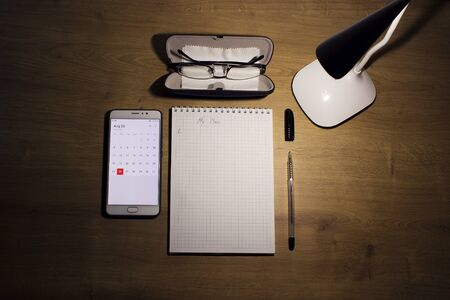 Education concept - notebook on a wooden table with hand written word plan, vision glasses in a case, pen and mobile phone with an open electronic calendar and a white lamp on top. Stok Fotoğraf