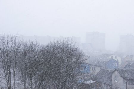 Strong wind and heavy snowfall blizzard in city at winter. Snow falls flakes on the street in the city. blur Imagens