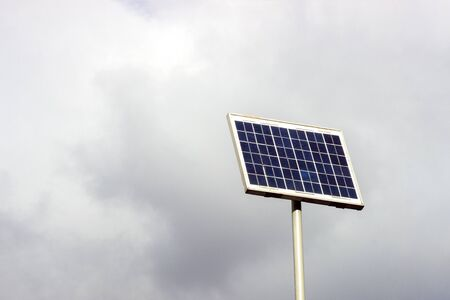 Electricity-generating solar panel on the background blue cloudy sky