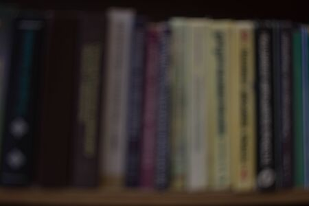 Blurred background with colorful books, university or college textbooks and fiction. Bookshelf at home or library. Concept for knowledge or education as well as imagination, creativity