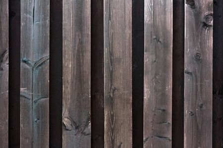 Old shabby wooden fence. Abstract pattern texture background. Brown faded boards. Oak bars, logs. Wood surface. Vertical stripes timber slats.