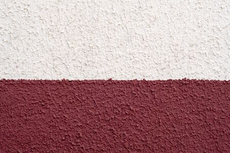 Ssurface of two-colored textured wall closeup. Abstract background consists of two stripes painted with red and white colors