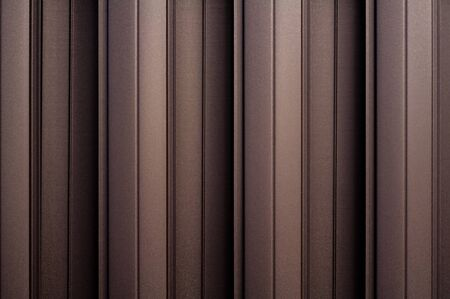 Matte brown metal wall siding background. Metal convex texture. Light brown striped surface. Abstract ribbed backgrounds