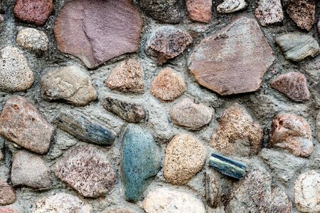 Background in the form of a fragment of a stone wall with textured stones from a colored rubble