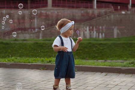 Beautiful little haired hair girl, has happy fun smiling face, pretty eyes, short hair, playing soap bubbles in white t-shirt. Child portrait. Creative concept. Stok Fotoğraf