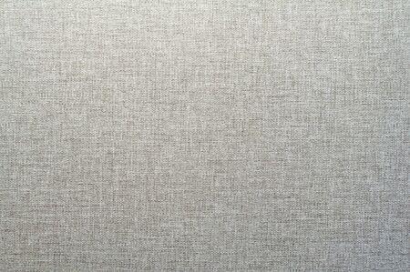 Texture di carta da parati grigia e bianca con un motivo spogliato. Superficie di carta grigia, primo piano della struttura. Fondale in vimini tessile.