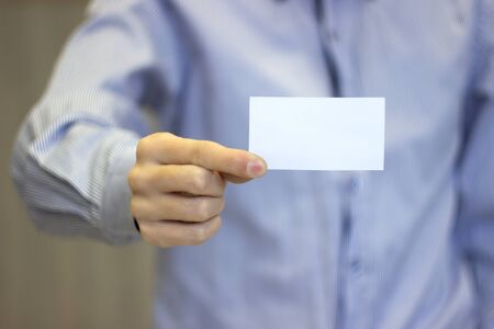 Close-up of business card in business man hand. businessman in shirt