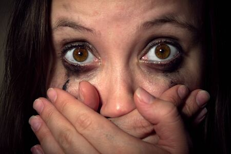 crying girl with leaking mascara in horror closes her mouth with her hands. violence against women, Concept freedom of speech, censorship, freedom of press. International Human Right day.