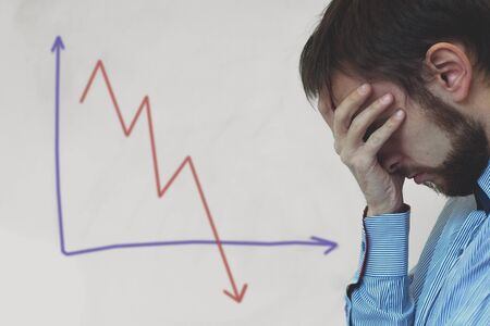 Frustrated business man standing near white board in office, covers his face with his hand at the falling graph of a stock market struck in financial crisis