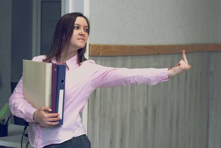 Business woman with documents in hand showing fuck off with the middle finger, leaving office.