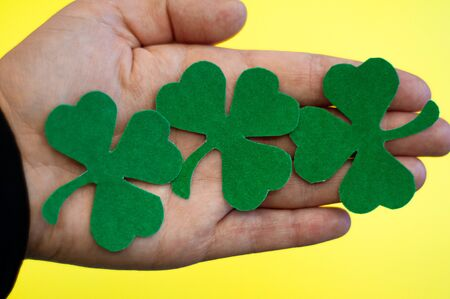 Paper green clover leas in hand on blurred background, St. Patricks day holiday symbol.