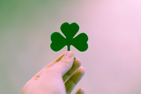 Green clover leas in hand on blurred background, St. Patricks day holiday symbol.