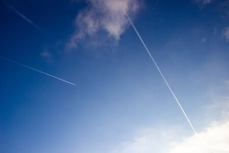 Airplane trails on blue sky. Stock fotó