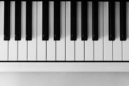 View from above of a piano keyboard on the upper half of frame. Copy space.