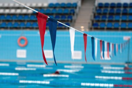 sport multi-color sling flags hanging over swimming pool, selective focus.