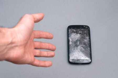 Man dropping his smartphone and trying to reach it. Phone screen is cracked and needs repairing.