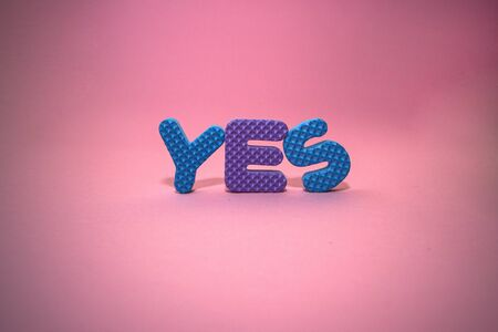 The word yes made of magnetic polystyrene letters.