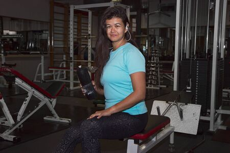 Attractive woman with dark long hair sits in the gym and holds a bottle of water Reklamní fotografie