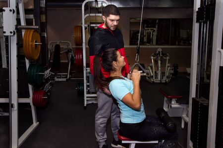 female with personal trainer doing pull ups on cable weight machine in cross fit training vintage fitness gym Foto de archivo