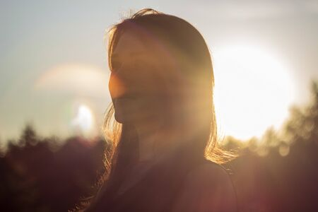 Close-up portrait of beautiful woman in the sunlight at sunset. enjoying warm and sunlight Banque d'images