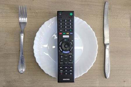 TV remote on a plate with cutlery. concept of mindless absorption of any information
