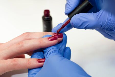 manicure specialist covers the nails with red varnish. close up