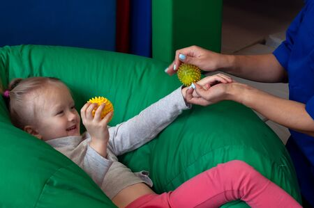 sensory therapist massaging little girl patient with a little ribbed ball