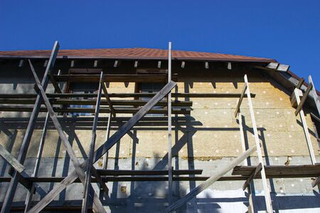 Unfinished residential home in construction progress at building site with scaffold