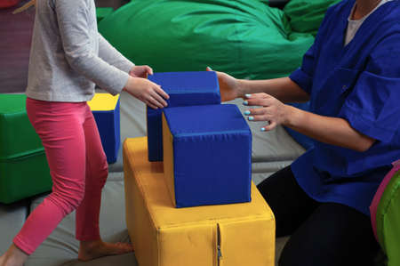 girl with a psychologist plays in multi-colored soft cubes. preschool education