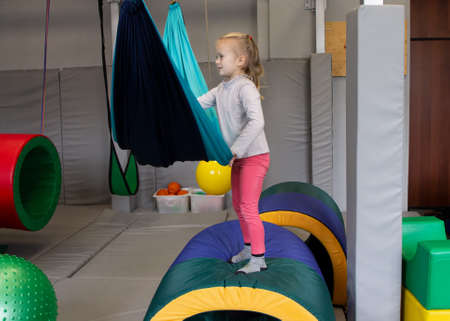 girl in tape made of elastic material. to replenish sensory experience, enhance tactile and muscular sensitivity, improve coordination and orientation in space, accelerate formation of body schema