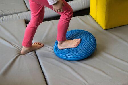Girl made exercises for sensory integration dysfunction. Sensory processing disorder. Stock Photo