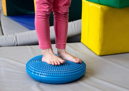 Girl made exercises for sensory integration dysfunction. Sensory processing disorder.