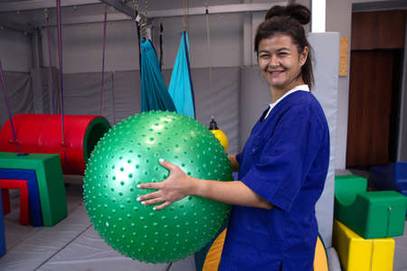 woman physiotherapist with fitball in rehabilitation center in working