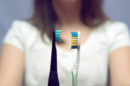 girl choosing between manual and electric toothbrushes