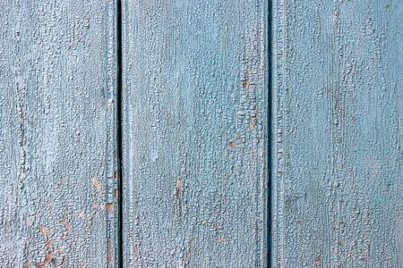 The texture of the old painted wall is covered with cracks and roughness close-up. Stock photo of old paint with cracks