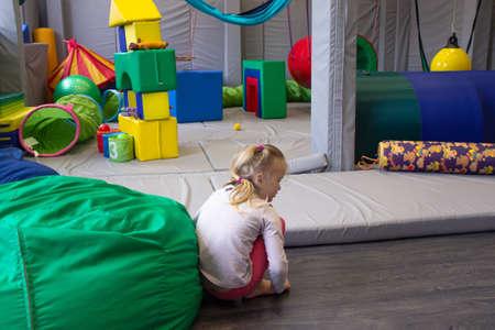 little girl plays in a sensory integration room on the floor Foto de archivo