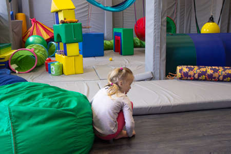 little girl plays in a sensory integration room on the floor