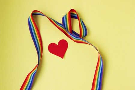 Red paper heart with rainbow ribbon on a yellow background. LGBT Valentines day. thanks to the medical staff for their work