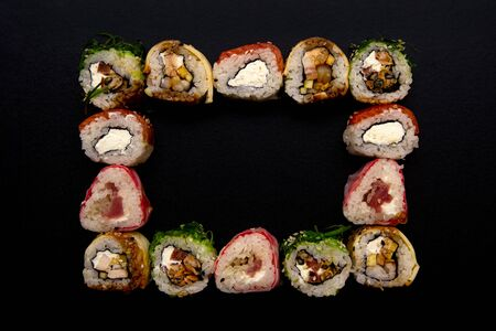 Sushi set in the square. frame with sushi on black background, top view.