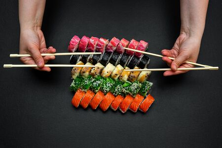 Large sushi set on a black plate background. A female hand holds two paar chopsticks. Top view