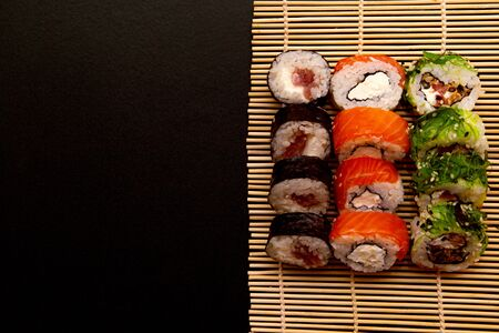 set of sushi roll on a bamboo plate or mat on a black background. three types of sushi of different colors and types, Futomaki, Uramaki and Hosomaki Stock Photo