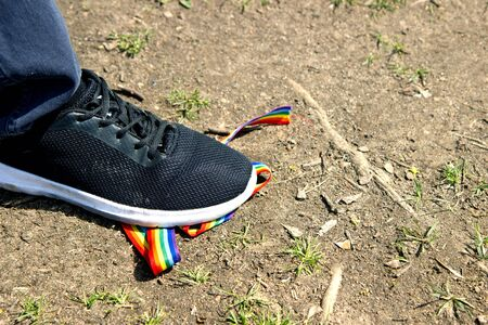 Trampling of LGBT flag in dirt by radical homophobe. Rainbow LGBT tape is stamped with feet.