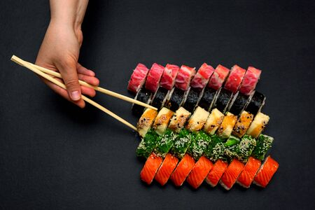 Big sushi set on a black plate background. A female hand holds two paar chopsticks. Top view