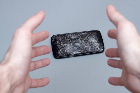 Man dropping his smartphone and trying to reach it. Phone screen is cracked and needs repairing. Stockfoto