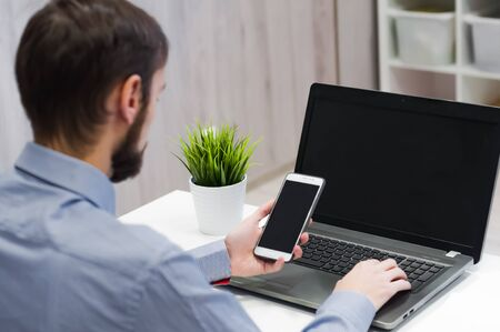 Close up male hands holding big smart phone, businessman using technology sitting at modern loft white desk, people and modern devices everywhere. 版權商用圖片
