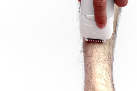 Man epilates his leg with an electric epilator device. close-up male fragment leg shaver shaving. Skin Care and Health. Hair Removal.
