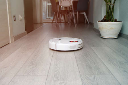 robot vacuum cleaner cleans the apartment. white robot vacuum cleaner work in interior