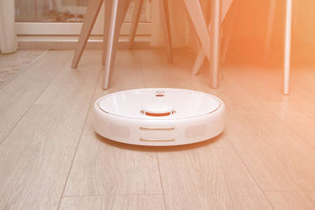 robot vacuum cleaner cleans the apartment. white robot vacuum cleaner work in interior